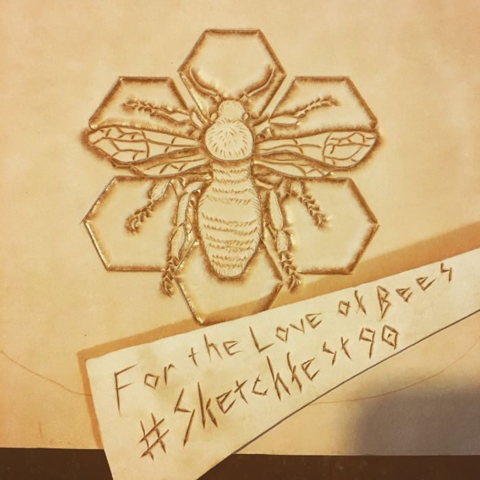 A bee has been tooled on a piece of undyed leather; the bee is depicted against six hexagons in a honeycomb pattern. Another piece of leather lays across this piece, with For the Love of Bees #Sketchfest 90 scratched into it.