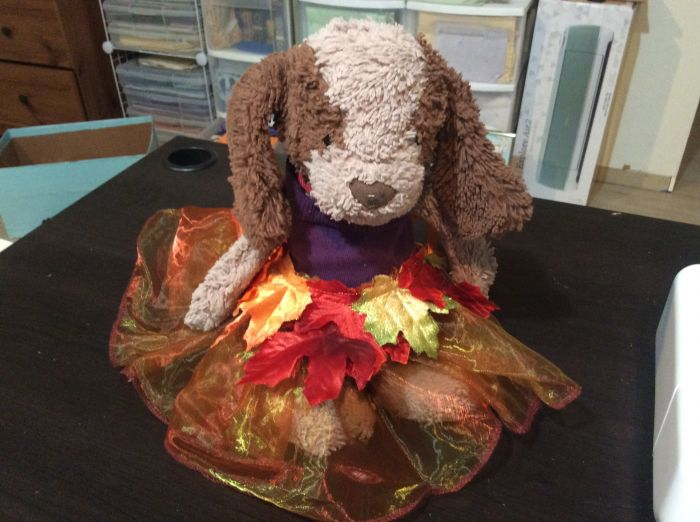A well-worn stuffed bunny plush wears a tutu made of glimmering, iridescent tulle in bronze and green, decorated by silk leaves in red, gold, and green-tinged gold. (This is a handicraft and not an illustration.)