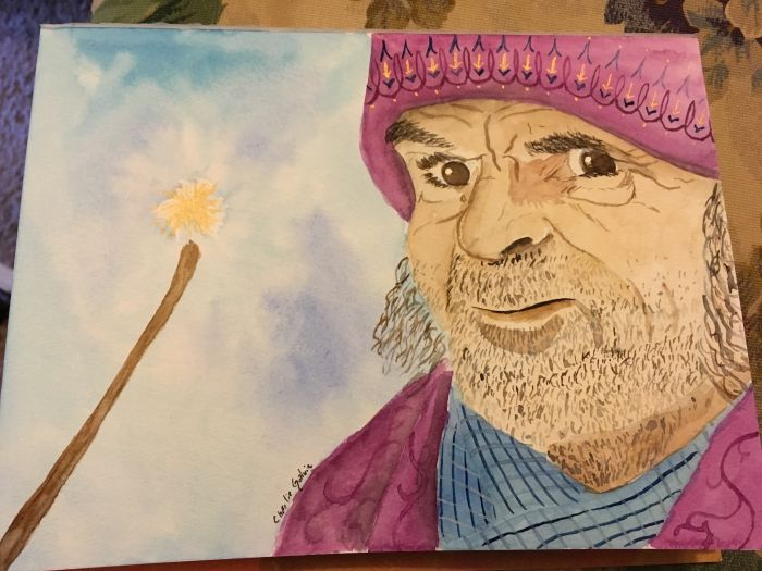 A wizard faces the viewer on the right side of the drawing, his cheeks and chin and visible neck covered in stubble. He seems to have mid-length hair or long sideburns. His face is lined, and he has a gruff expression on his face. His brown eyes almost glare at the viewer. He's wearing a purple knit hat with golden arrows pointing down detailed along the edge; it's pulled down over a wrinkled forehead. He may be wearing a blue plaid scarf, along with a purple jacket or robe - you only see it from the shoulders. A wand is held aloft, sloping in from the left side of the page - held aloft by the wizard, no doubt. The wand is brown, and there's a poof of golden magic floating above its tip.